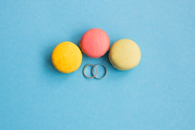 青の背景にマカロンの近くの結婚指輪。 copyplace、テキストのための場所。