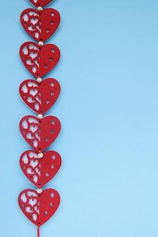 青の背景に赤の心。心とバレンタインデーの背景。 copyplace、テキストとロゴのスペース。