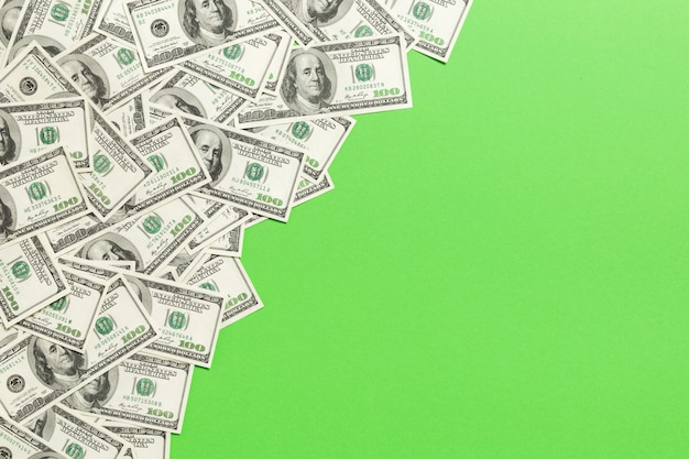 Copyspaceの上に色の机の上のトップビュー紙幣。真ん中にお金のスタックを持つ100ドル札。ビジネスのトップビュー