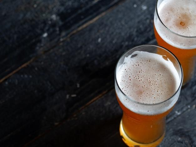 Copyspaceの背景を持つ木製のテーブルの上のガラスの2つの冷たいビール