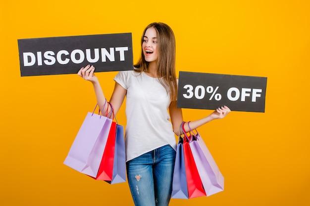 カラフルな買い物袋とcopyspaceテキスト割引30%記号バナー黄色で分離された美しいブルネットの女性