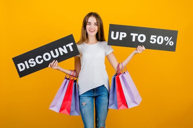 カラフルなショッピングバッグとcopyspaceテキスト割引50%サインバナー黄色で分離された美しいブルネットの女性