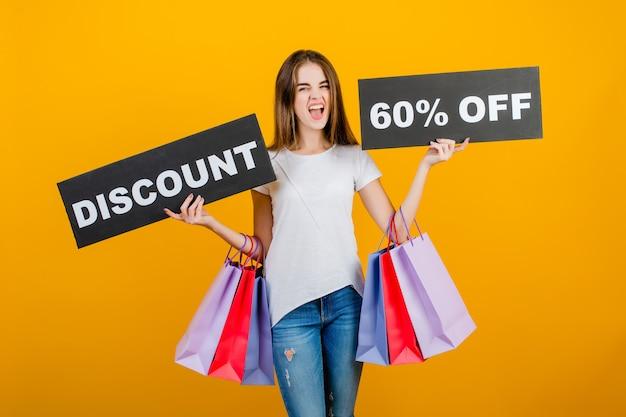 カラフルなショッピングバッグとcopyspaceテキスト割引60%サインバナー黄色で分離された美しいブルネットの女性