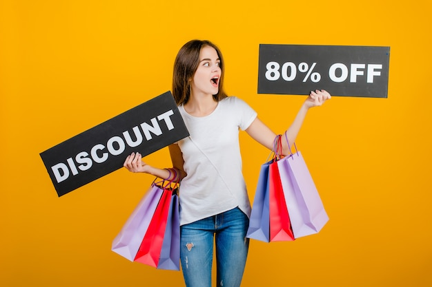 カラフルなショッピングバッグとcopyspaceテキスト割引80%記号バナー黄色で分離された美しいブルネットの女性