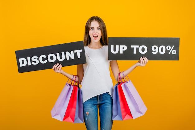 カラフルなショッピングバッグとcopyspaceテキスト割引90%記号バナー黄色で分離された美しいブルネットの女性