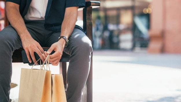 The copyspace of close up of man hand holding shopping bags.