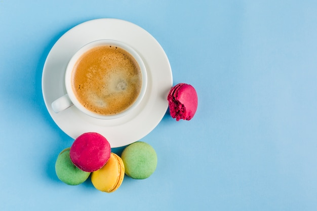 青いcopyspace、平面図、フラットcopyspaceにコーヒーの白いカップと色とりどりのマカロン