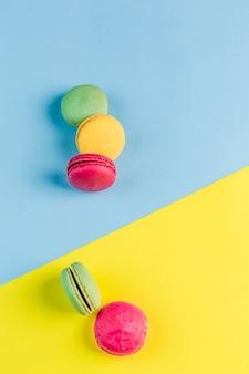 Разноцветные миндальное печенье на синий и желтый copyspace, вид сверху, флэтли с copyspace