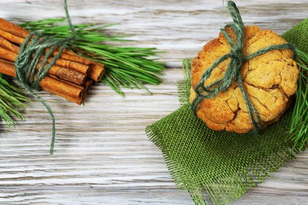 木製、copyspaceのfir小枝で飾られたジンジャーブレッドクッキーとシナモンスティックのヒープ。上からの眺め