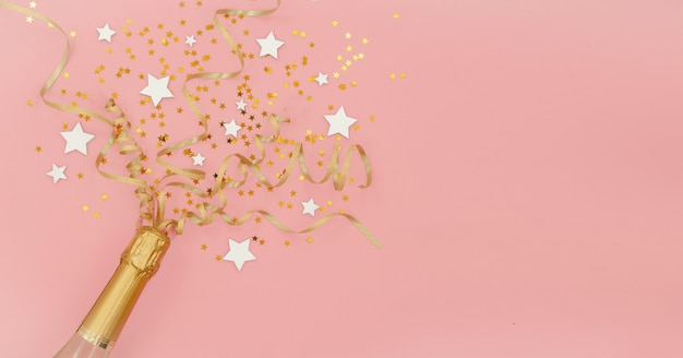 Бутылка шампанского с конфетти звездами и золотой вечеринки растяжки на розовый абстрактный фон. новый год, рождество, день рождения или свадьба концепции. верхний горизонтальный вид copyspace flat lay.