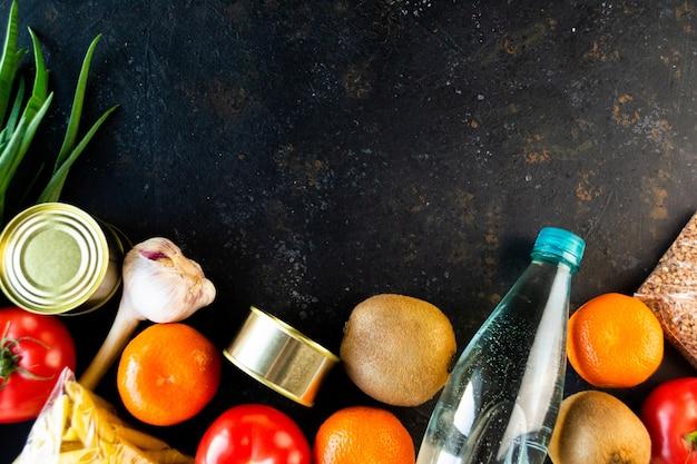 Продовольственный карантин продовольственного кризиса продовольствия изолирован на черном фоне конкретных. зерновые, консервы, макароны, фрукты, овощи, вода. концепция доставки еды, пожертвования, благотворительность. copyspace.flat lay