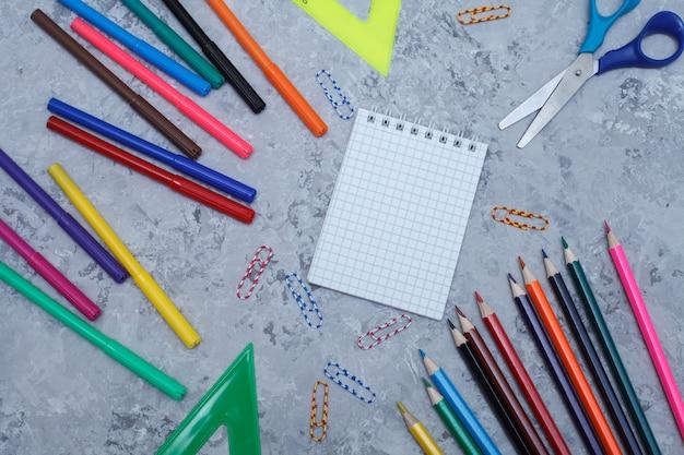 色鉛筆、フェルトペン、白いシート、クリップ、はさみ、定規は、灰色の背景、copyspaceにあります。トップビュー、フラットlay.template。オフィスアクセサリー