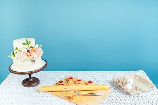 Copyspace 흉내낸 작업 공간 베이커 제과 셰프 크림색 흰색 2단 결혼 생일 케이크, 테이블에 신선한 꽃, 파란색 배경 스튜디오에 있는 쿠키