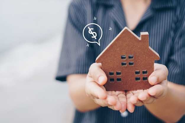 女性が抱く小さな家のコピースペースモデル