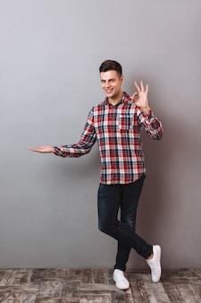シャツとジーンズの手のひらにcopyspaceを押しながら見ながらokサインを示す笑みを浮かべて男の完全な長さの画像