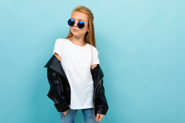 Copyspace photo of cool stylish schoolgirl on a blue background in a white t-shirt and a black jacket