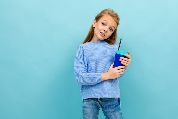 Copyspace photo of girl in a blue sweater against a blue wall with a glass of cocoa