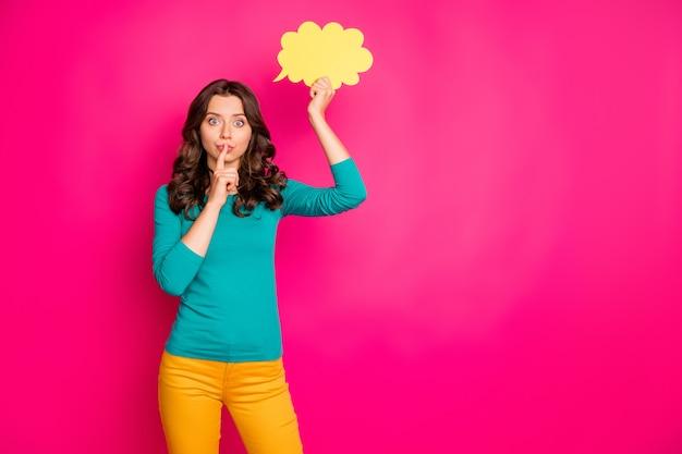 Copyspace фотография модной кудрявой волнистой подруги, показывающей вам знак тсс, чтобы перестать обсуждать мысли героя в желтом пузыре, изолированном розовом ярком цветном фоне