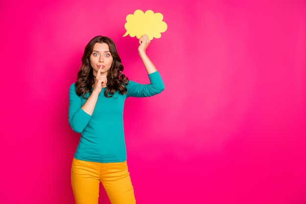 Copyspace photo of trendy curly wavy girlfriend showing you shh sign to stop discussing ger thoughts in yellow bubble isolated pink vivid color background