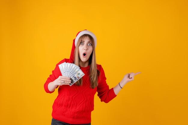 Счастливые деньги доллара девушки в руке указывая на copyspace нося шляпу santa