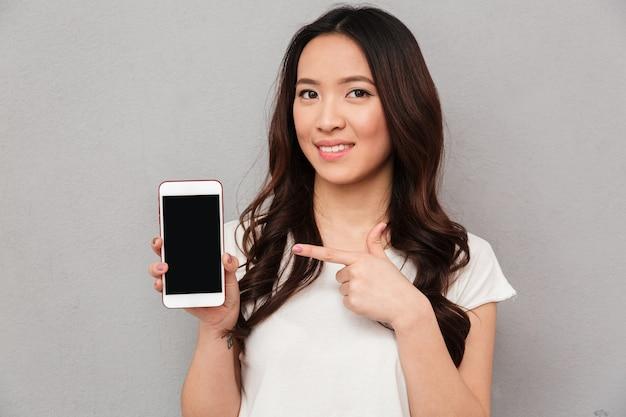 Фото крупного плана азиатской женщины в вскользь футболке демонстрируя экран copyspace современного smartphone, изолированный над серой стеной
