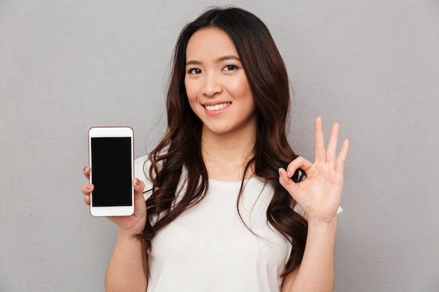 Фото крупного плана китайской женщины в вскользь футболке демонстрируя экран copyspace современного smartphone и показывая одобренный знак, изолированный над серой стеной
