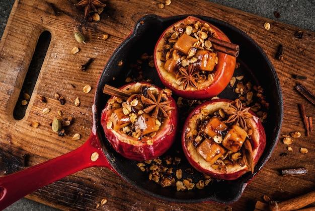 秋の料理のレシピ。グラノーラ、タフィー、スパイスを詰めた焼きりんご。黒い石のテーブル、フライパン、copyspace top viewfed焼きりんご