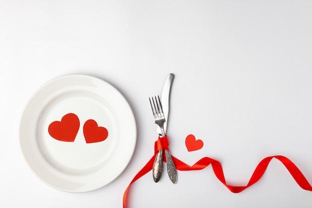 白い背景の上のロマンチックなテーブルセッティング。バレンタインの日カードテンプレート。赤いリボン、プレート、銀器、ビンテージフォーク、ハート、ナイフ。コンセプト周年、誕生日、テキストのための場所、copyspace topview。