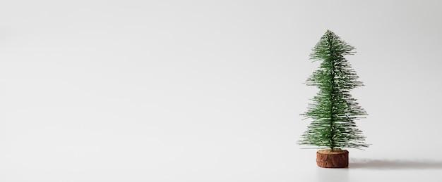 Copyspaceと白い背景の上のwebバナーミニチュアクリスマスツリー