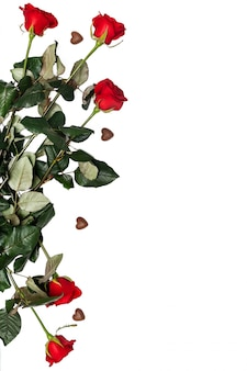 チョコレート菓子と赤いバラはcopyspaceで分離されました。ロマンチックなバレンタインデー。ハート型の花とキャンディー