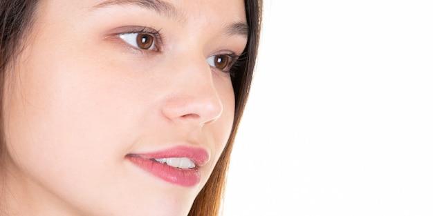 Молодой естественный портрет крупного плана женщины усмехаясь в белизне с copyspace