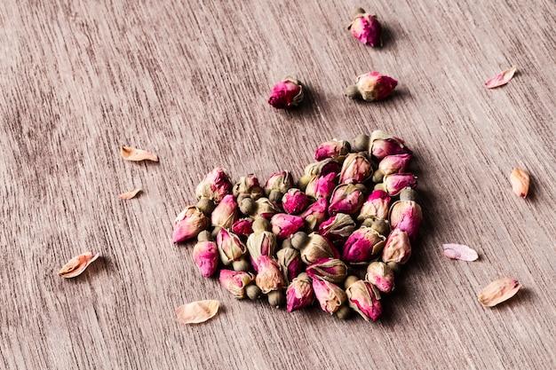 ピンク赤乾燥バラの蕾ハートcopyspaceと古い木製のテーブルの上。