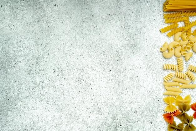Виды сырой пасты. макароны пенне, фузилли, фарфалле, спагетти, чиффери сушат на светлом бетонном фоне ... плоская планировка, вид сверху, copyspace