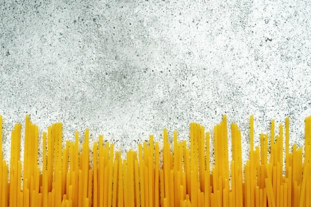 Виды сырой пасты. макаронные изделия спагетти сушат на светлом фоне бетона. , плоская планировка, вид сверху, copyspace