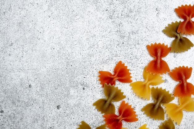 Виды сырой пасты. зеленые, желтые и красные макароны фарфалле сушат на светлом бетонном фоне. , плоская планировка, вид сверху, copyspace