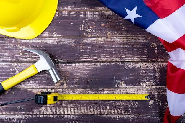 労働者の日アメリカコンセプト、フラグアメリカ、copyspaceと木製の背景上の様々なツールのセット