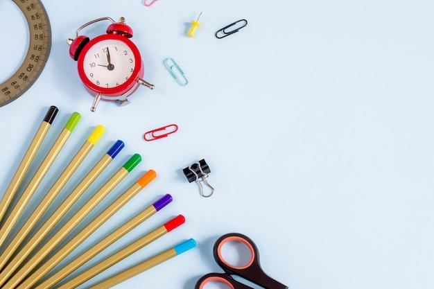 設計のためのcopyspaceと青色の背景色の学用品。鉛筆、はさみ、ノート、目覚まし時計、トップビュー。学校に戻る