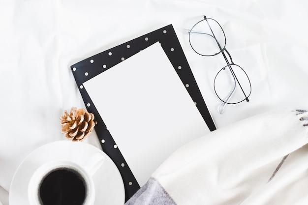 ベッド、眼鏡、スカーフ、白いコーヒーカップに白い紙。 copyspaceで冬フラットレイアウト