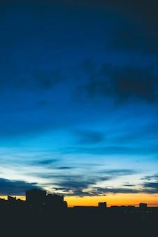 Городской пейзаж с прекрасным разноцветным ярким рассветом. удивительное драматическое синее облачное небо над темными силуэтами городских зданий. атмосфера оранжевого восхода в пасмурную погоду. copyspace.