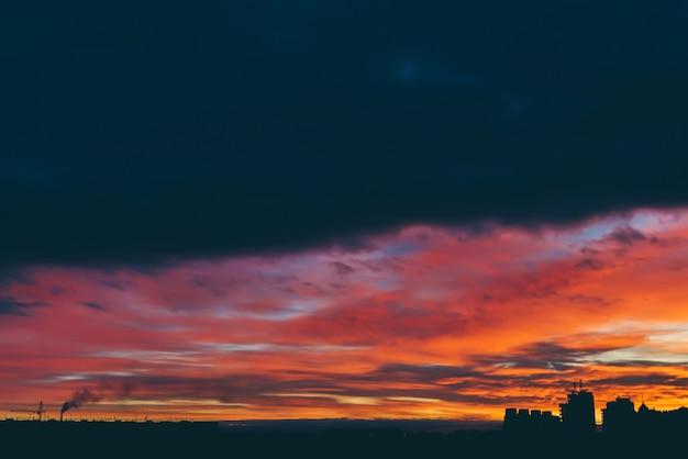 素晴らしい密生鮮やかな夜明けの街並み。都市の建物の暗いシルエットの上の驚くべき劇的な色とりどりの曇り空。どんよりした天気の日の出の雰囲気。 copyspace。