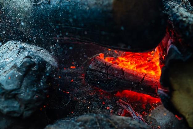 くすぶった丸太が鮮やかな火で燃えた。キャンプファイヤーのオレンジ色の炎の雰囲気。 copyspaceで内側からのき火の想像を絶する詳細な画像。煙と灰の旋風がクローズアップ。