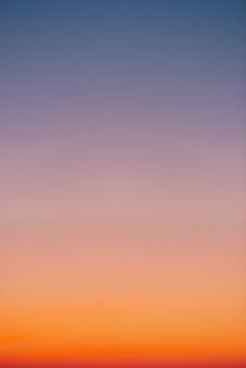 オレンジ色の地平線と紫の雰囲気の夜明け前の澄んだ空。滑らかなオレンジバイオレットグラデーション夜明けの空。一日の始まり。早朝にcopyspaceで天国。日没、日の出の背景