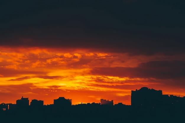 鮮やかな燃えるような夜明けの街並み。都市の建物の暗いシルエットの上に驚くほど暖かい劇的な曇り空。オレンジ色の日光。どんよりした天気の日の出の大気の背景。 copyspace。