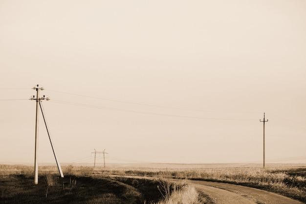 セピア色の空の下で未舗装の道路とフィールドの電力線と大気の風景。 copyspaceと電気柱の背景画像。高電圧のワイヤ。モノクロの電気産業。
