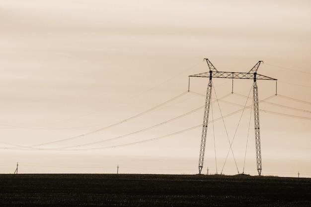 空のクローズアップの背景の電力線。セピア色のトーンでcopyspaceと電柱のシルエット。地上の高電圧のワイヤ。モノクロの電気産業。