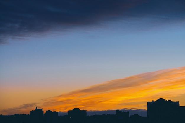 Городской пейзаж с прекрасным разноцветным ярким рассветом. удивительное драматическое синее облачное небо над темными силуэтами крыш городских зданий. атмосферная предпосылка оранжевого восхода солнца в пасмурную погоду. copyspace