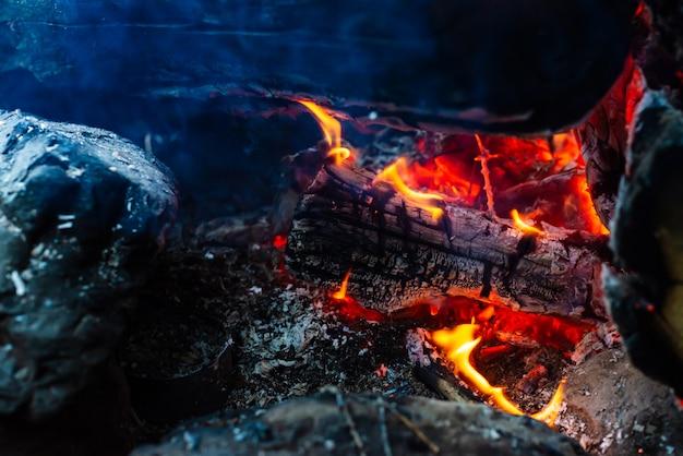 くすぶった丸太が鮮やかな火で燃えた。キャンプファイヤーのオレンジ色の炎と大気の背景。 copyspaceで内側からのき火の想像を絶する詳細な画像。煙と灰がクローズアップ。