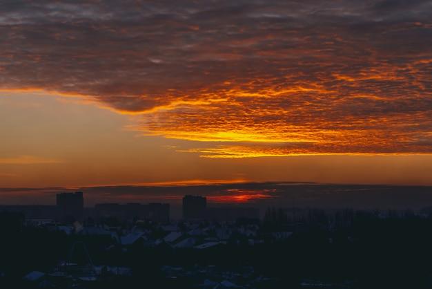 鮮やかな燃えるような夜明けの街並み。都市の建物の屋根の暗いシルエットの上の驚くほどの暖かい劇的な曇り空。オレンジ色の日光。どんよりした天気の日の出の大気の背景。 copyspace。