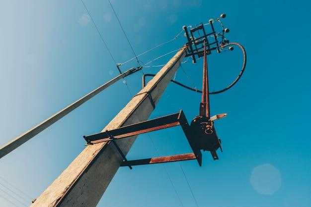 Линии электропередач на предпосылке конца-вверх голубого неба. электрический концентратор на шесте. электрооборудование с copyspace. провода высокого напряжения в небе. электроэнергетика.