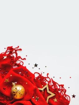 クリスマスと新年の背景。金色の星と白い背景の紙吹雪と明るい赤いスカーフ。 copyspaceで折り畳まれた暖かいアクセサリー。